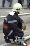 Firefighter. A firefighterat a fire, crouching beside three hose valves, ready to operate them. The legs of spectators can be seen in the background Stock Image