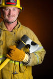 Firefighter. Smiling hero firefighter with axe Stock Photography