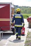 Firefighter. In uniform carrying fire extinguisher Royalty Free Stock Photos