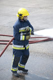 Firefighter. Using fire hose outdoors Royalty Free Stock Image