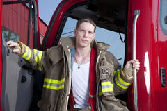 Firefighter. A fireman standing in the door of a fire truck royalty free stock photos
