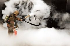 Firefighter. Extinguishing small fuel tank fire Stock Photography