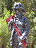 Firefighter. Statue of a firefighter in protective gear with red axe in front of Poudre Canyon Fire Station, Colorado Royalty Free Stock Photos