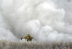 Firefighter. Standing in front of huge cloud of smoke Royalty Free Stock Photos