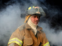 Firefighter. Volunteer firefighter in uniform amidst smoke Royalty Free Stock Photo