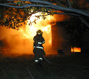 Firefighter. A firefighter battles a blaze at an abandoned house royalty free stock photo