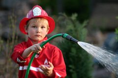 Firefighter. Little boy as firefighter in uniform royalty free stock images