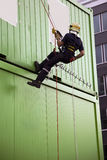 Firefighter abseiling. Fireman abseiling on the side of green containers during a drill royalty free stock photos