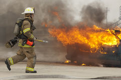 Firefighter in action. Firefighter running toward vehicle on fire. This was a drill exercise Royalty Free Stock Photo