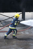 Firefighter in action. Firefighter using fire hose outdoors Royalty Free Stock Image