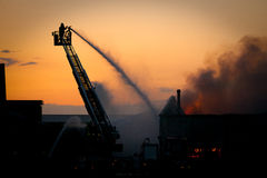Firefighter in action. Firefighter working from a ladder truck Royalty Free Stock Images