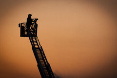 Firefighter in action. Firefighter in silhouette, working from a ladder truck Royalty Free Stock Photography