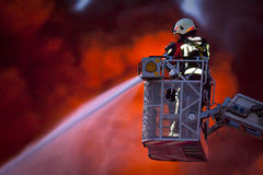 Firefighter in action. Firefighter working from a ladder truck Stock Photos