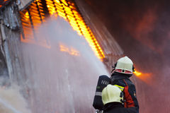 Firefighter in action. Firefighter in front of a huge fire Royalty Free Stock Photos