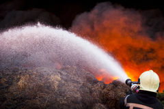 Firefighter in action. Firefighter in front of a huge fire Stock Images