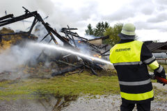 Firefighter in action at burning house Stock Image