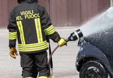Firefighter in action with foam to put out the fire Royalty Free Stock Image