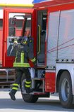 Firefighter in action jump down quickly from the fire truck Stock Photo