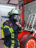 Firefighter in action and with oxygen bottle and mask - Serie Firefighter Royalty Free Stock Images