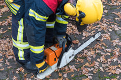 Firefighter in action and turn on the chain saw Royalty Free Stock Photo
