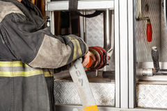 Firefighter Adjusting Water Hose In Truck Stock Photos