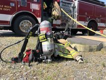 Firefighter air tank, hose and truck at the ready Stock Photography