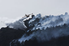 Firefighter aircraft in Spain forest fire. An aircraft firefighter in Spain against forest fires, canadair 415, Model CL415, throw water to extinguish Royalty Free Stock Images