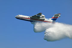 Firefighter airplane. Airplane spraying water over fire stock photography