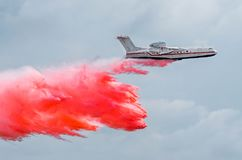 Firefighter airplane drops red water on a fire in the forest. Royalty Free Stock Images