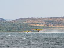 Firefighter airplane, water bomber, air tank taking water from t Royalty Free Stock Photo