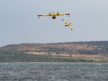 Firefighter airplane, water bomber, air tank taking water from t Royalty Free Stock Images
