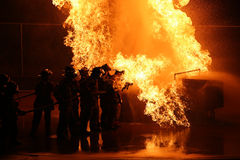 Firefighter Battle Heat Flame. Firefighters heroically work against heat and danger to gain control of the billowing flames of a burning object Stock Photos