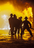 Firefighter bracing during firefighting. Firefighter bracing with a hose Stock Images