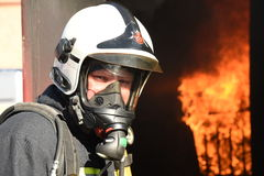 Firefighter in breathing apparatus BA BASCA. Firefighter in breathing apparatus prepares to enter a burning building. Fire and flames royalty free stock image