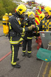 Firefighter in breathing gear. England. May 2012. Firefighters in breathing apparatus are checked out by their controller stock images