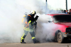 Firefighter and burning car Stock Images