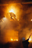 Firefighter and burning man Royalty Free Stock Image