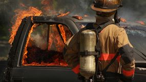 Firefighter With Burning Truck. Firefighter looks to a truck cab engulfed in flames with broken windows Stock Photo