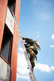 Firefighter climb on fire stairs Stock Photos