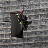 Firefighter climbing a wall. Of a house during the fire drill Royalty Free Stock Images