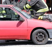 Firefighter cuts the windshield  of car with a Hacksaw Royalty Free Stock Photography