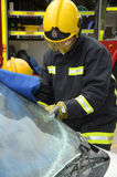 Firefighter cutting away a windscreen at car crash royalty free stock image