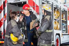 Firefighter Discussing With Colleagues Against Stock Images