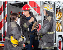 Firefighter Discussing With Colleagues At Fire Royalty Free Stock Image