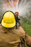 Firefighter dousing house fire. Firefighter fireman sitting on ground aiming fire hose towards burning home Royalty Free Stock Photos