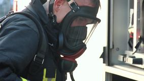 Firefighter dressed in uniform and an oxygen mask. A fire in an apartment building.