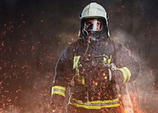 A firefighter dressed in a uniform in a studio. A professional firefighter dressed in uniform and an oxygen mask standing in fire sparks and smoke over a dark royalty free stock image