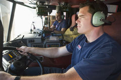 A firefighter driving a fire engine Stock Photo