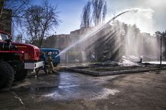 Firefighter and emergency situations mimic the fire on the background of a fire truck on a Sunny day. Photo royalty free stock photo