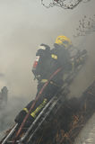 Firefighter engulfed in thick smoke. Hoses down a fire in an historic thatch roof cottage Stock Images